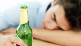 young man asleep on a table while holding an empty beer bottle