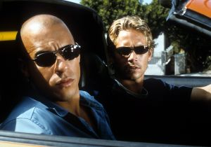 Vin Diesel and Paul Walker looking from car in a scene from the film 'The Fast And The Furious', 2001.