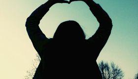Woman Making Heart Shape Against Clear Sky