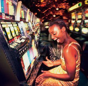 Young woman winning money from slot machine, profile