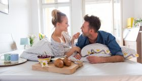 Happy couple eating breakfast in the bed at home