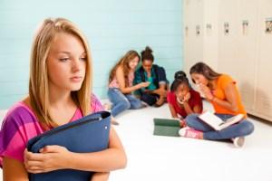 Teenage girls cyber-bully classmate. Gossip, talking. School hall. Lockers.