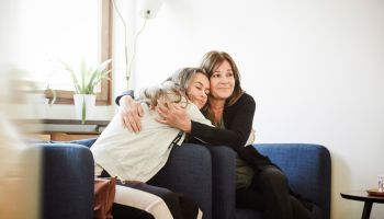 Mother and daughter embracing while sitting at wellness center