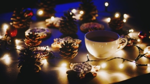 Close-Up Of Coffee Cup And Gingerbread Cookies Amidst Illuminated Christmas Lights