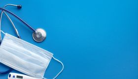 Protective Disposable Medical Face Mask, Stethoscope And Thermometer On A Blue Background.