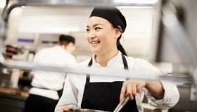 Smiling female chef stirring pot in kitchen at restaurant