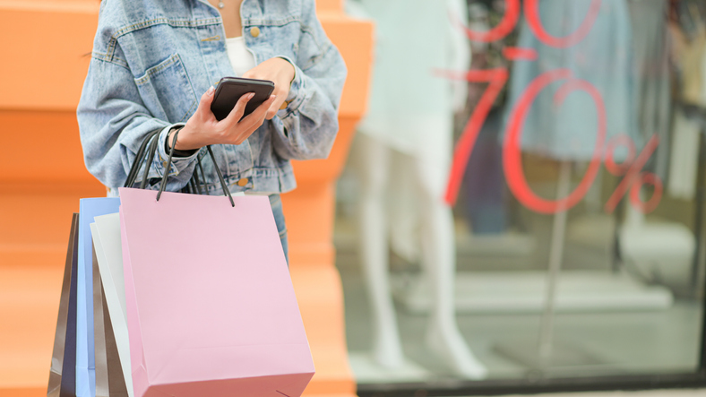 Midsection Of Woman Using Mobile Phone In City