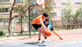 Young asian male adults playing basketball outdoors